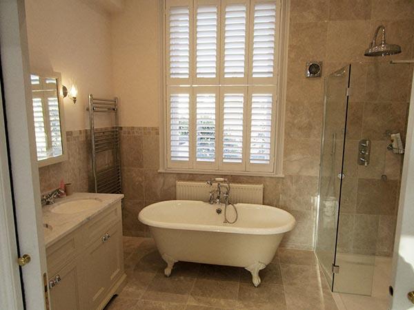 Ensuite bathroom marble roll top bath shower screen